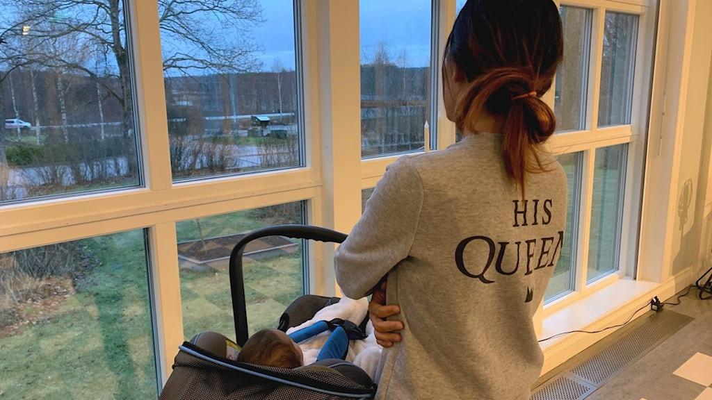 En ung kvinna står med ryggen till och tittar ut genom ett fönster. Över armen hänger en babykorg med en liten baby i.
