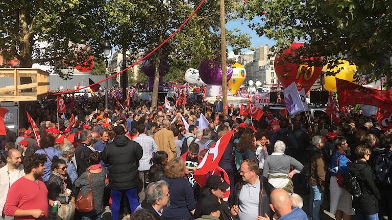 Personer med flaggor och banderoller går på en gata.