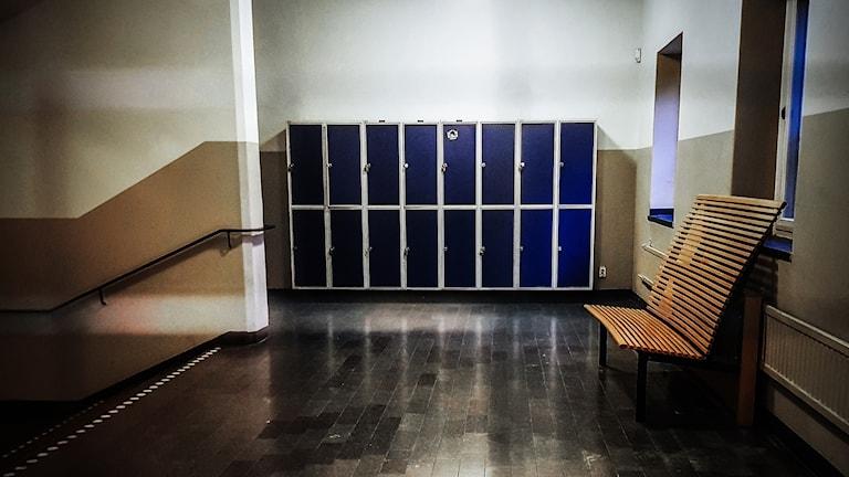 Bild på skåp och en tom bänk inne i en skola.