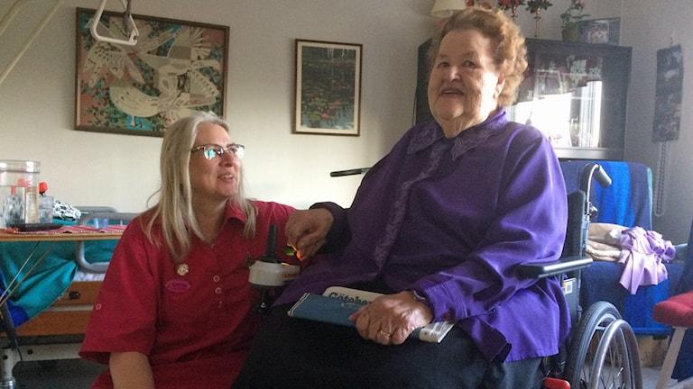 Sköterska och kvinna i rullstol.