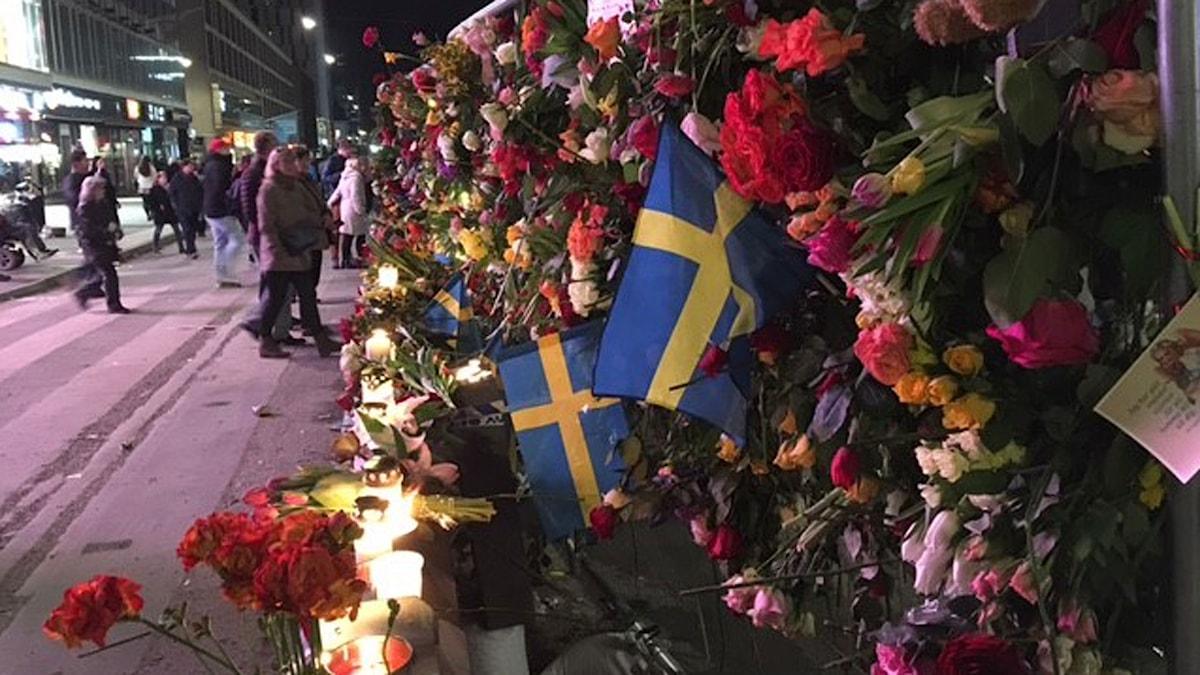 Blommor, ljus och svenska flaggor vid Drottninggatan.