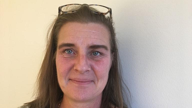 Fotot visar en kvinna med glasögon på huvudet.