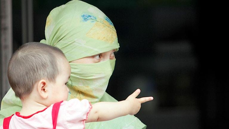 En uigurisk kvinna med ett barn i sin famn.