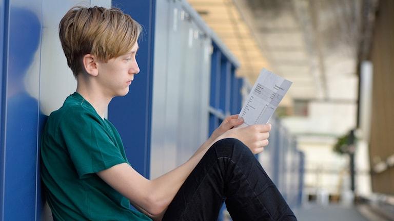 Pojke tittar på sina betyg