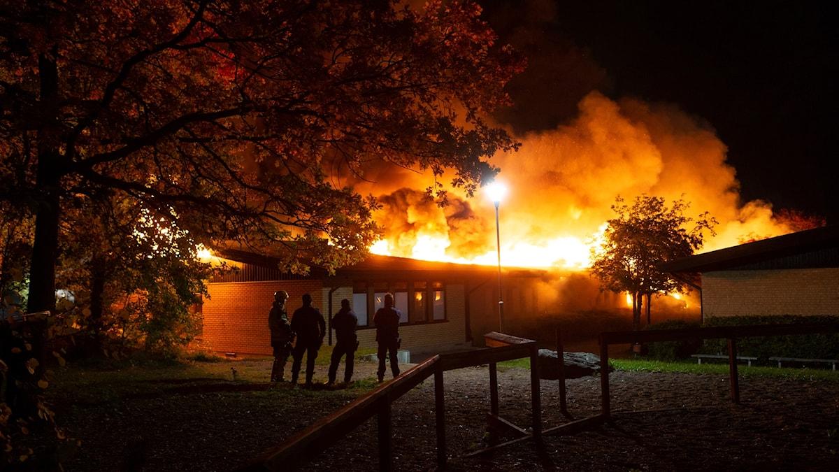 Gottsundaskolan i Uppsala brinner. Några människor står och tittar på på avstånd.