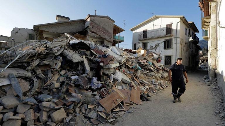 En man går i resterna av byn Santi Lorenzo e Flaviano efter jordskalvet.