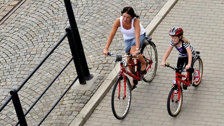 Barn med cykelhjälm cyklar med sin mamma på en cykelbana.