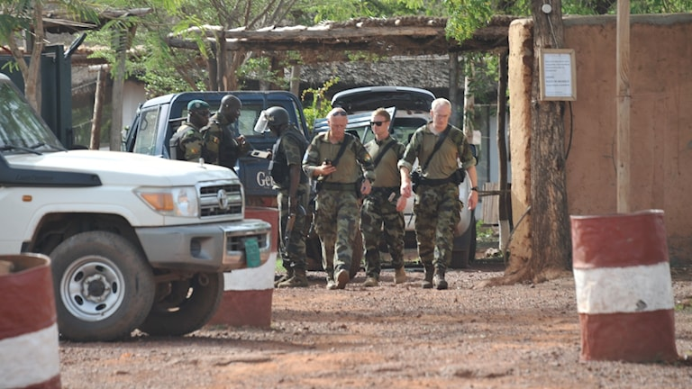 European and Malian forces walk at the entrance of the Kangaba tourist resort on the edge of Bamako on June 19, 2017