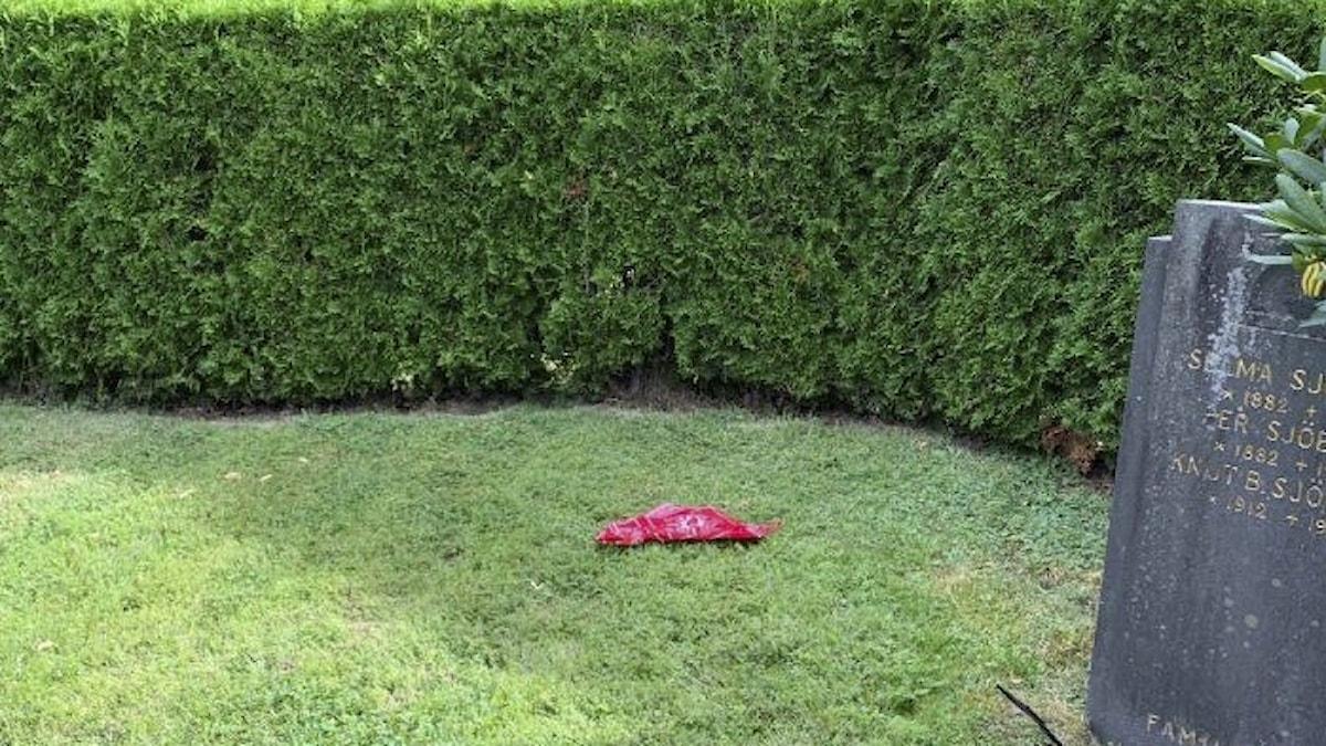ett rött tygstycke vid en grav.