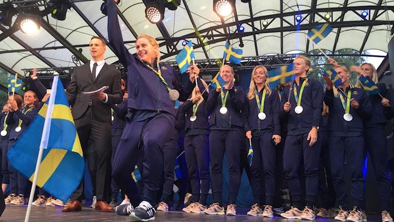 Damlandslaget tar emot folkets jubel på scenen i Kungsträdgården.