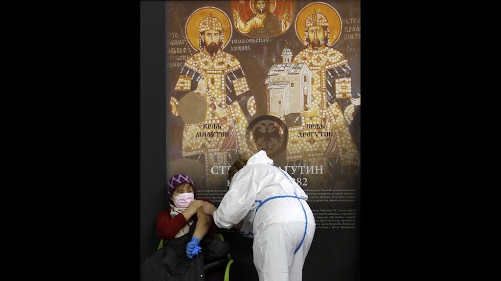 Kvinna vaccineras framför ikonmålning
