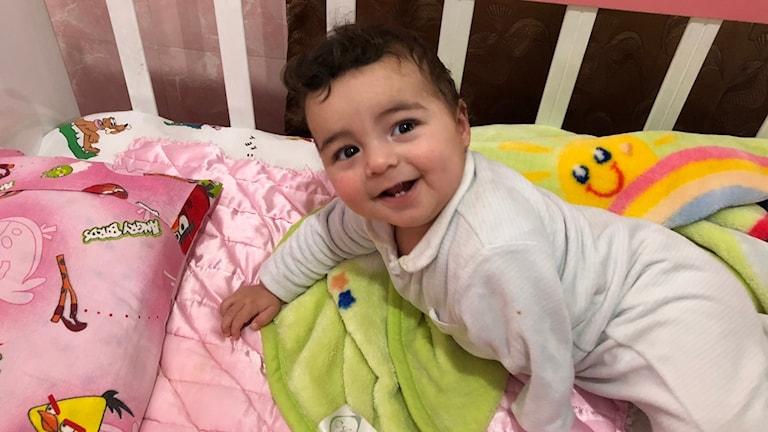 Lycklig bebis i en spjälsäng.