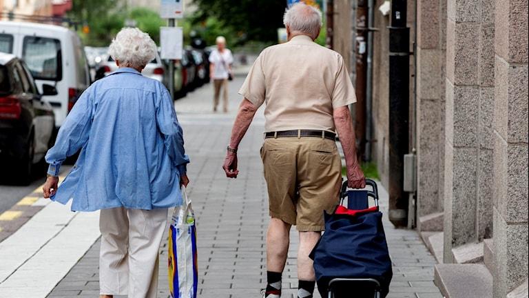 En kvinna och en man går på gata.
