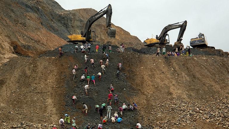 Grävskopor och människor som samlar stenar