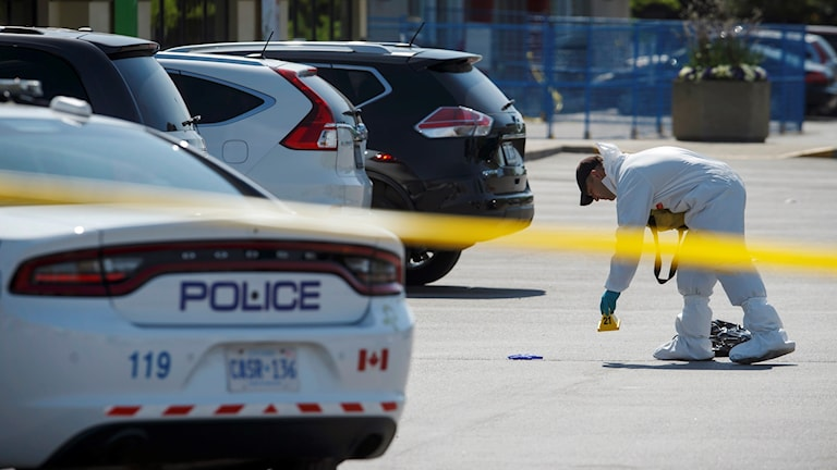 En kanadensisk polisbil bakom avspärrning och i bakgrunden undersöks en brottsscen.