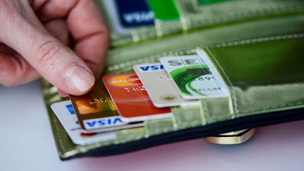 Hand tar betalkort från plånbok.