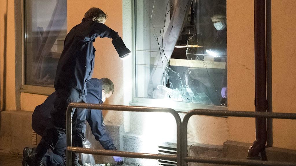 Bilden visar polisens kriminaltekniker som arbetar vid den krossade rutan till nattklubben i centrala Ängelholm. Foto: Johan Nilsson/TT.