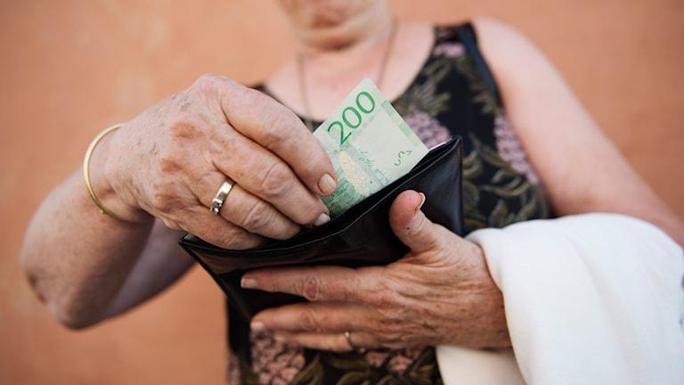 Kvinna lägger 200-kronorssedel i plånbok.