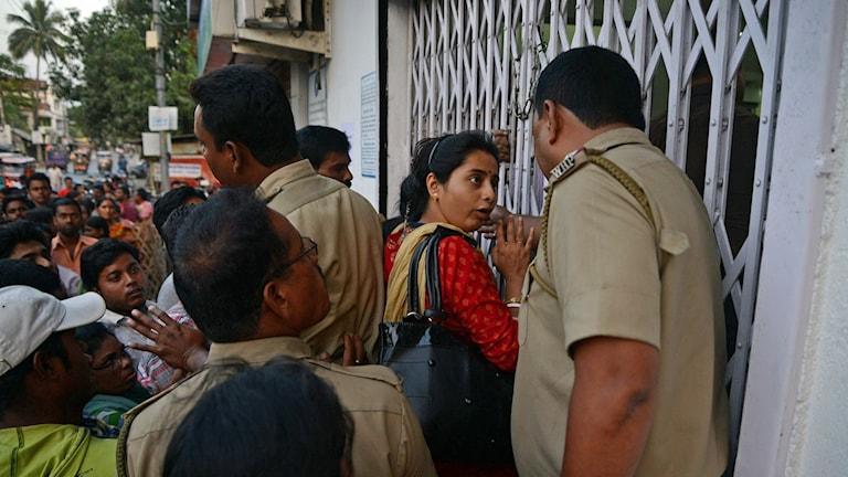 Polis försöker lugna köande bankkunder som vill byta in de numera ogiltiga sedlarna i Siliguri i nordöstra Indien.