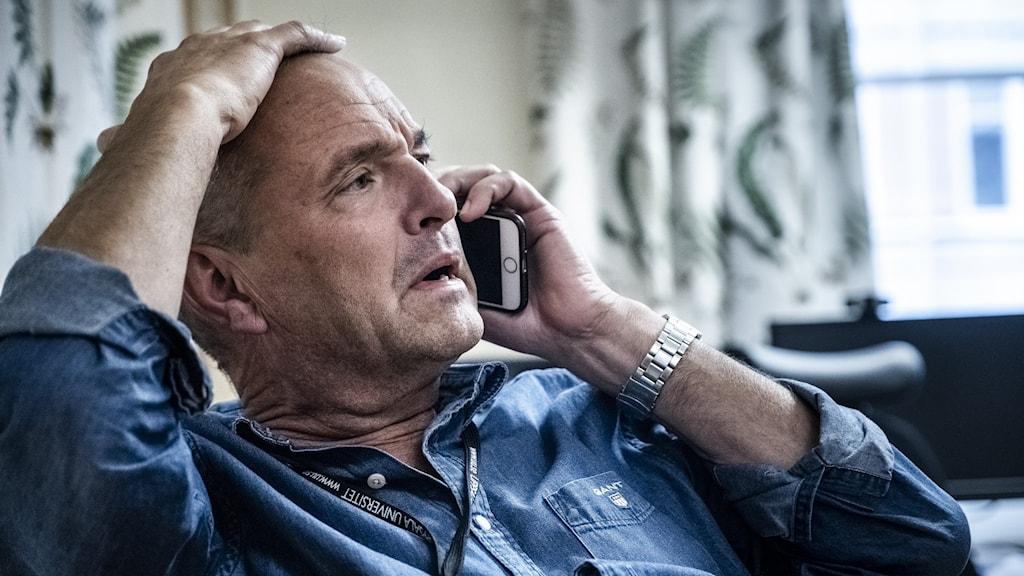 Överläkare Björn Olsen sitter och talar i telefon.
