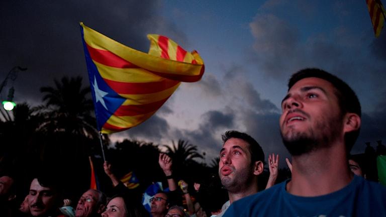 Personer bredvid en katalansk flagga.