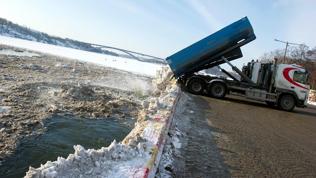 Lastbilar tippar snö vid från kajen på Norrmälarstrand ner i Mälaren i centrala Stockholm.
