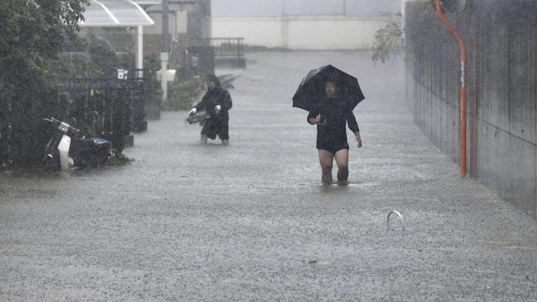 Personer tar sig fram på översvämmade gator under tyfonen Hagibis, i Shizuoka, centrala Japan Lördag 12 oktober 2019.