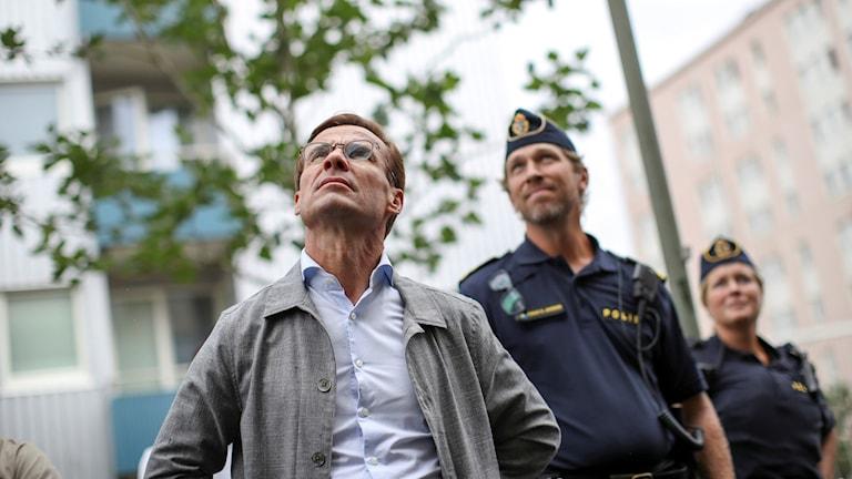 Ulf Kristersson med två poliser i bakgrunden