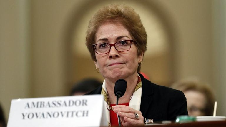 """Kvinna bakom mikrofon och skylt där det står """"Ambassador Yovanovitch"""""""