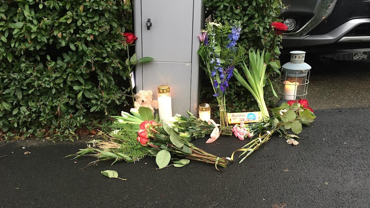 Bilden visar blommor och gravljus som ställts vid brevlådan till huset där en familj i Bjärred hittades döda på kvällen den 9 januari 2018. Foto: Anna Bubenko/Sveriges Radio.