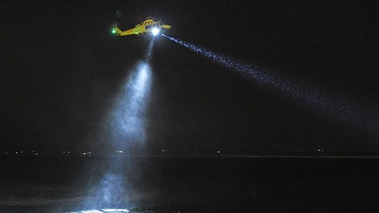Helikopter med strålkastare över mörkt hav.