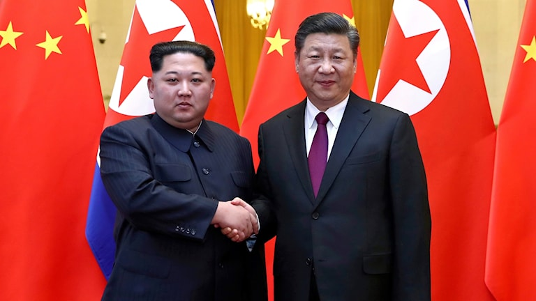 Nordkoreas ledare Kim Jong-Un skakar hand med kinas president Xi Jingping.