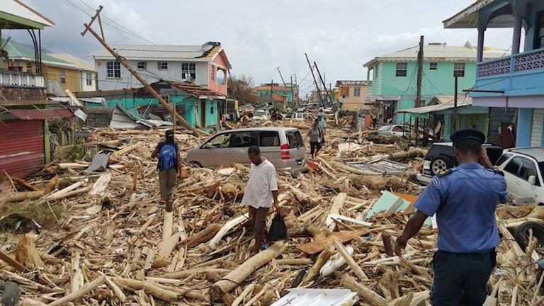Bråte ligger på en gata med förstörda hus.