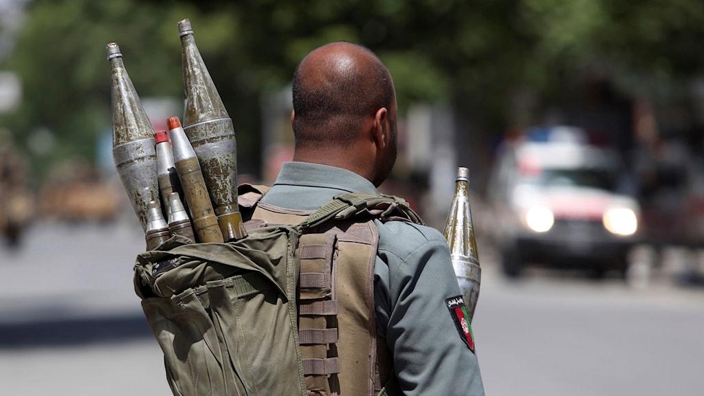 En person ur den afghanska säkerhetsstyrkan står på en plats där en självmordsbombning ägde rum tidigare i maj.