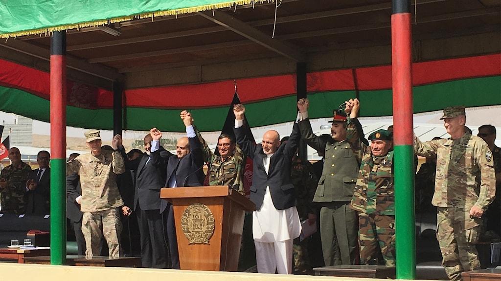 Afghanistans president står vid ett podium med händerna i luften