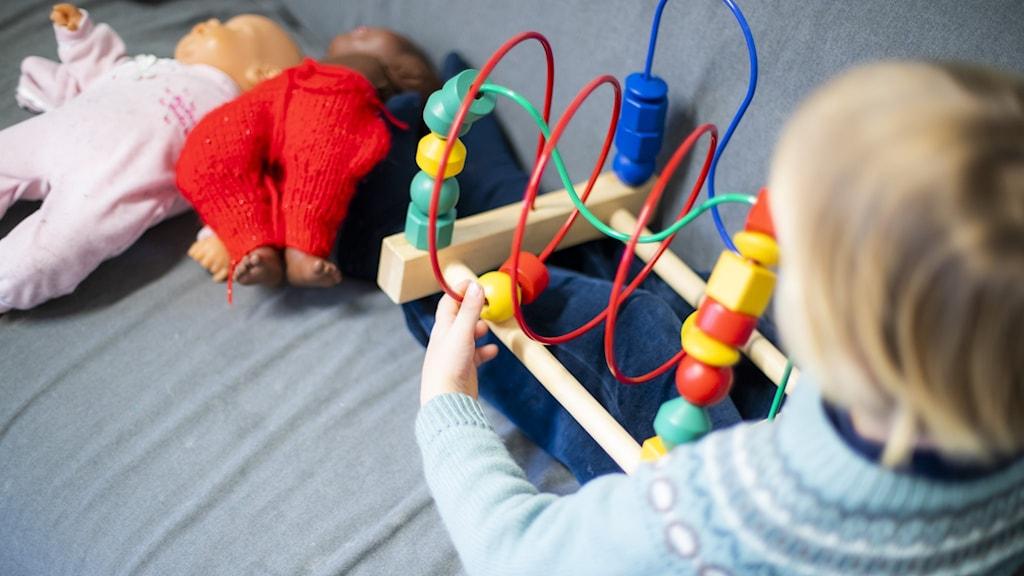 Barn med blont hår i förskoleåldern med leksaker i en soffa