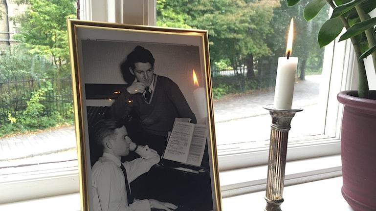 Bilden visar ett tänt ljus som står bredvid ett foto av Hans Alfredson, tillsammans med Patrick Meurling på 50-talet. På Thomanderska studenthemmet i Lund. Foto: Anna Bubenko/Sveriges Radio.