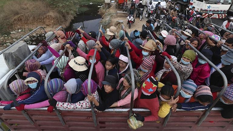 Textilarbetare på ett lastbilsflak.