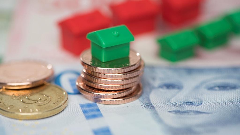 Mynt och sedlar och monopolhus på ett bord.
