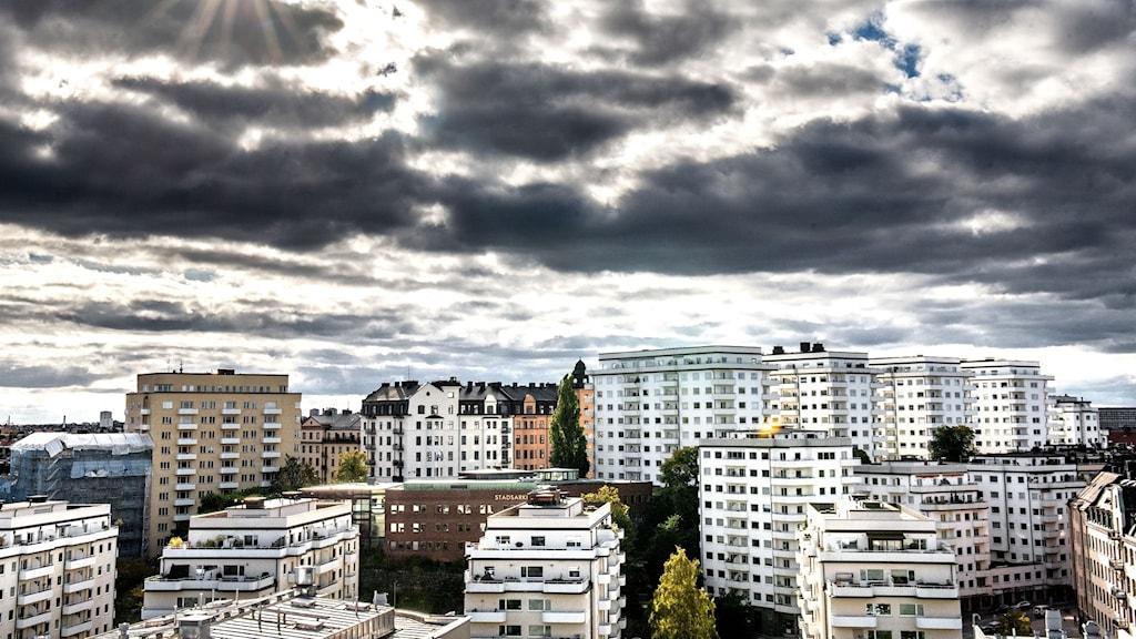 Stora moln där solen spricker igenom, över bostäder