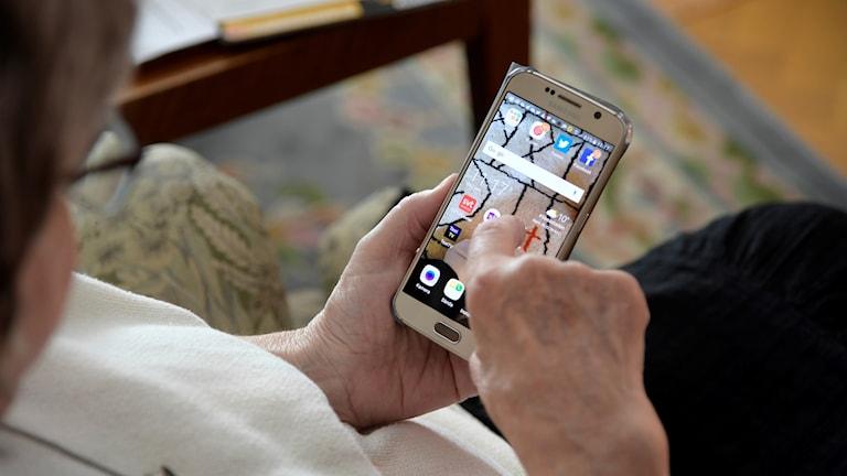 Äldre kvinna surfar på smartphone