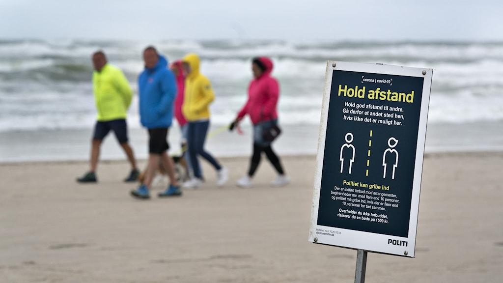 Skylt som uppmanar till avståndshållning på strand i Danmark