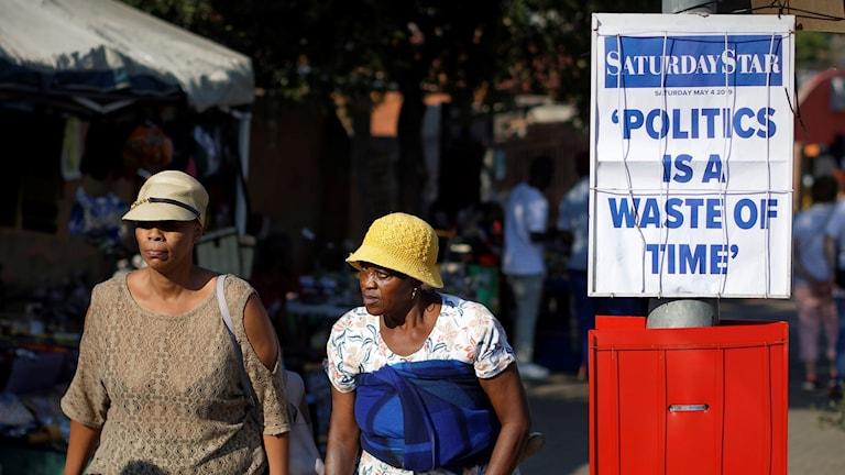 """Två kvinnor går förbi en skylt med texten """"Politik är slöseri med tid"""""""