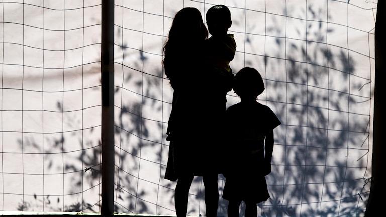Silhuett på en mor och två barn.