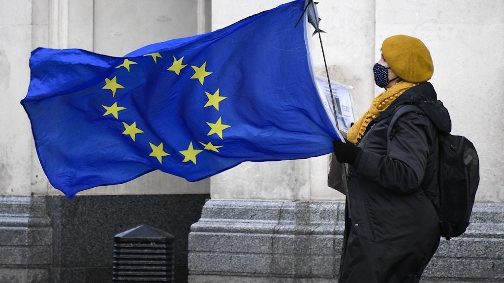 Kvinna vid en EU-flagga.