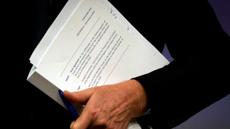 Det 585 sidor långa utkastet till ett brexitavtal under armen på EU:s chefsförhandlare Michel Barnier.