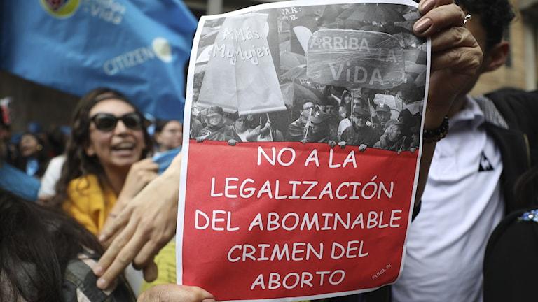 """Demonstrant håller upp en poster med texten """"Nej till legalisering av abort"""""""
