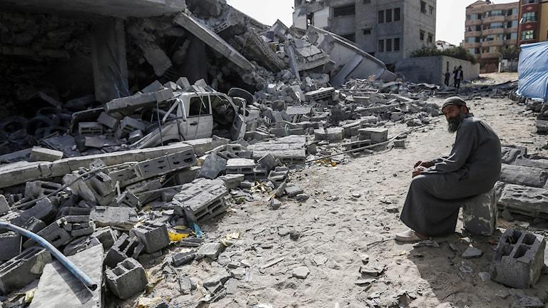En man sitter vid resterna av en byggnad i Gaza City efter helgens våldsamheter.