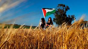 Palestinska kvinnor viftar med den palestinska flaggan under demonstrationen på påskafton.