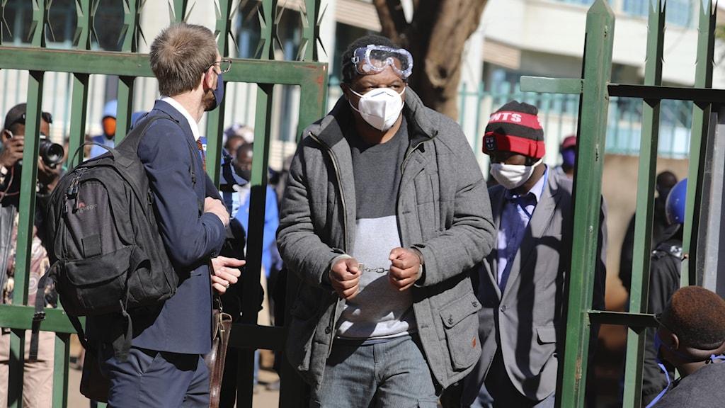 Färgad man med munskydd och handbojor håller upp ett dokument.